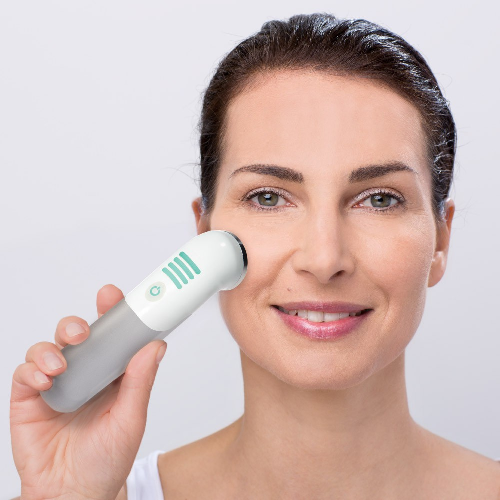 Woman using Use the Mira-Skin ActiveBooster wand for skin rejuvenation in her face